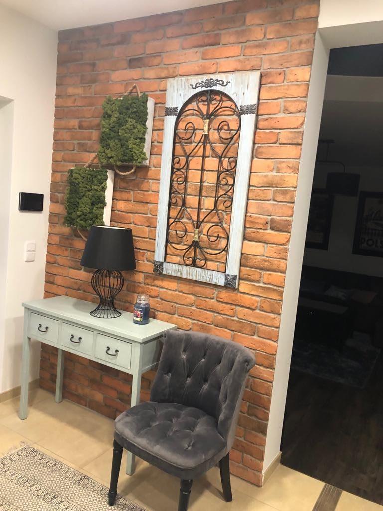 Przedpokój, cegła na ścianie i piękny fotel wykonany na zamówienie
